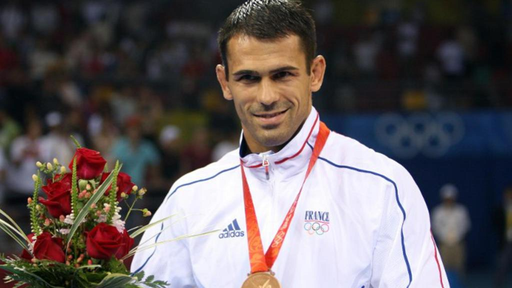 Bronze medalist Christophe Guenot of France pose on the podium of the men's Greco-Roman 74 kg wrestling category during the 2008 Beijing Olympic Games on August 13, 2008 in Beijing. Manuchar Kvirkelia of Georgia won gold, Chang Yongxiang of China won silver and Yavor Yanakiev of Bulgaria and Christophe Guenot of France claimed bronze. AFP PHOTO / VALERY HACHE / AFP / VALERY HACHE